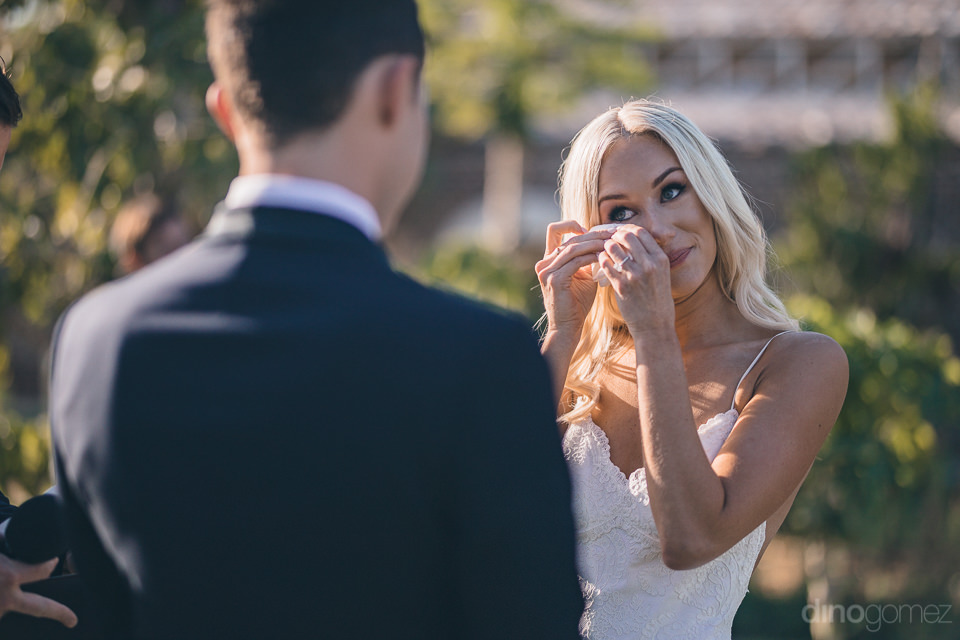 the bride cries tears of joy while standing at the altar getting