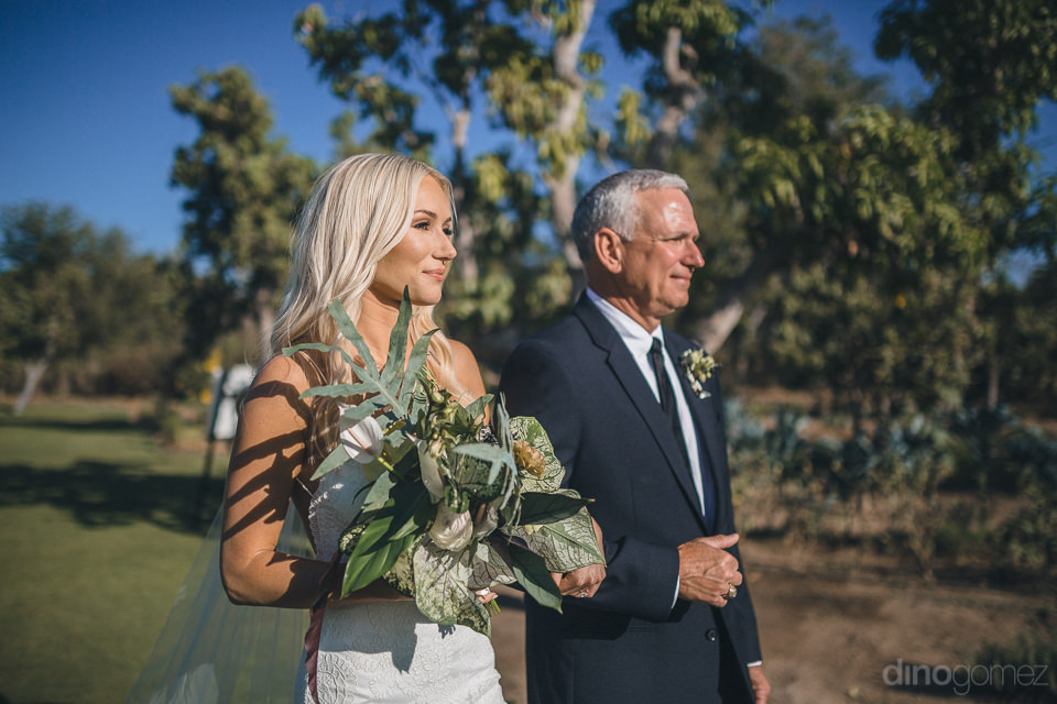 bride and father walk down aisle bride holding bouquet by pina h