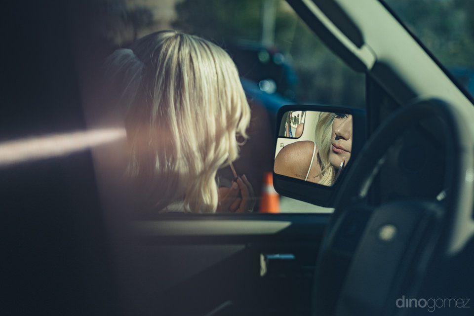 bride looks at herself in side-view mirror of car moments before