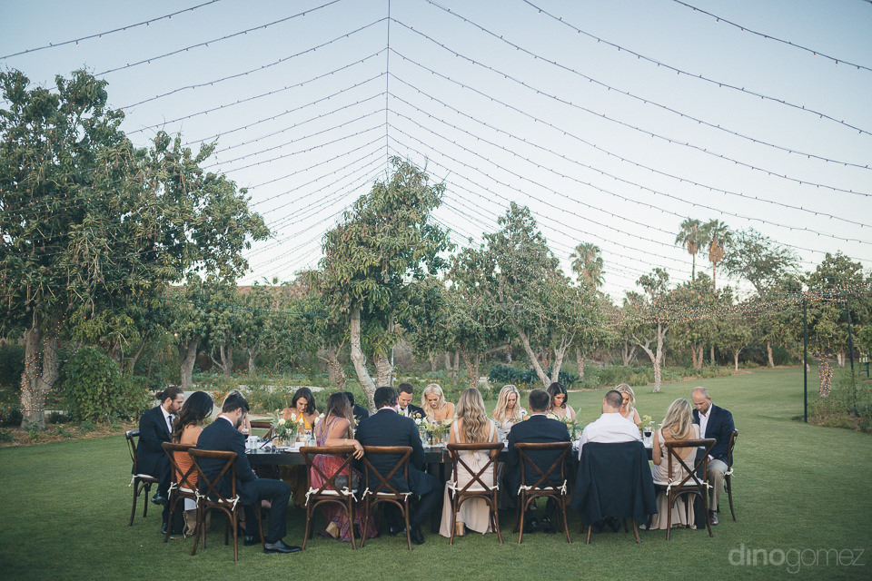 wedding guests eat dinner outdoors at destination farm wedding i