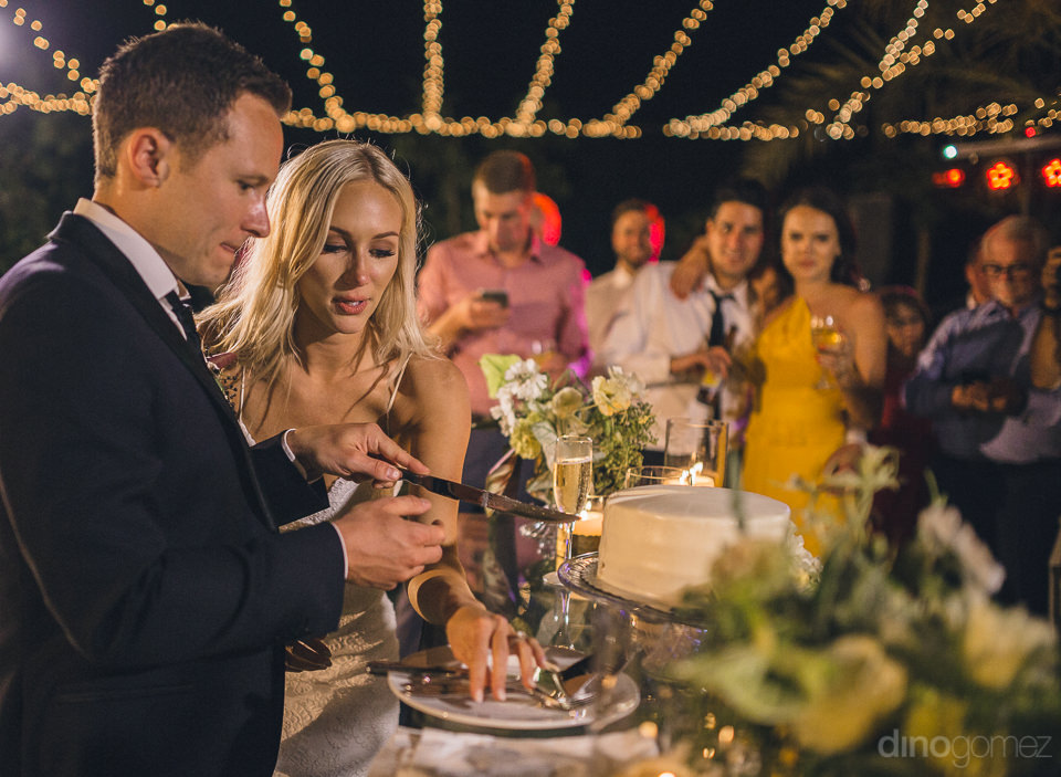 cutting the wedding cake at luxury boho wedding at flora farms i