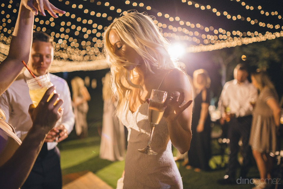 bride dances with groom while holding champagne glass