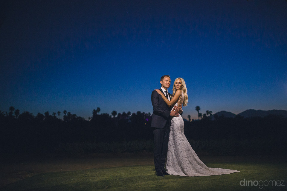 stunningly beautiful wedding photo of newlyweds at twilight in f