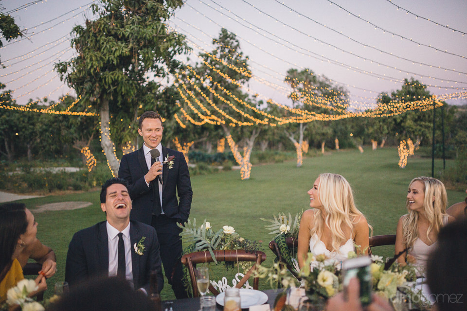 groom speaks to laughing guests at wedding dinner at flora farms