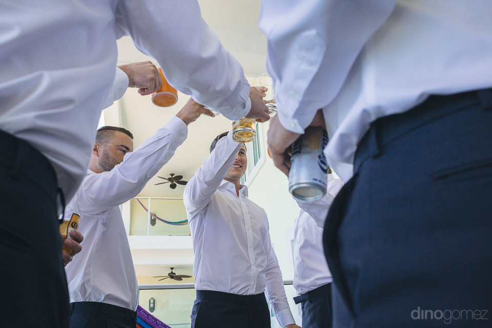 groomsmen drink corona beer before mexico wedding