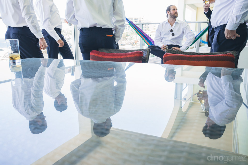 groomsmen reflected in glass table in artistic wedding photo