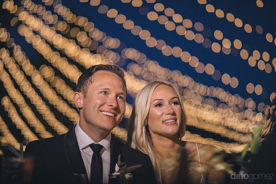 smiling newlyweds and hanging lights in classy wedding photo by