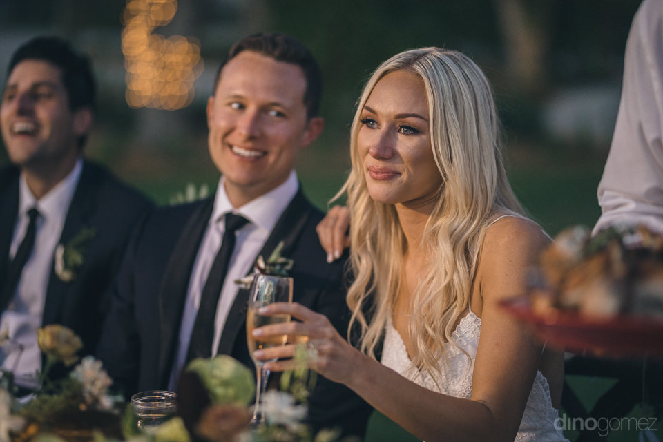 newlyweds smile at dinner during speeches given by guests
