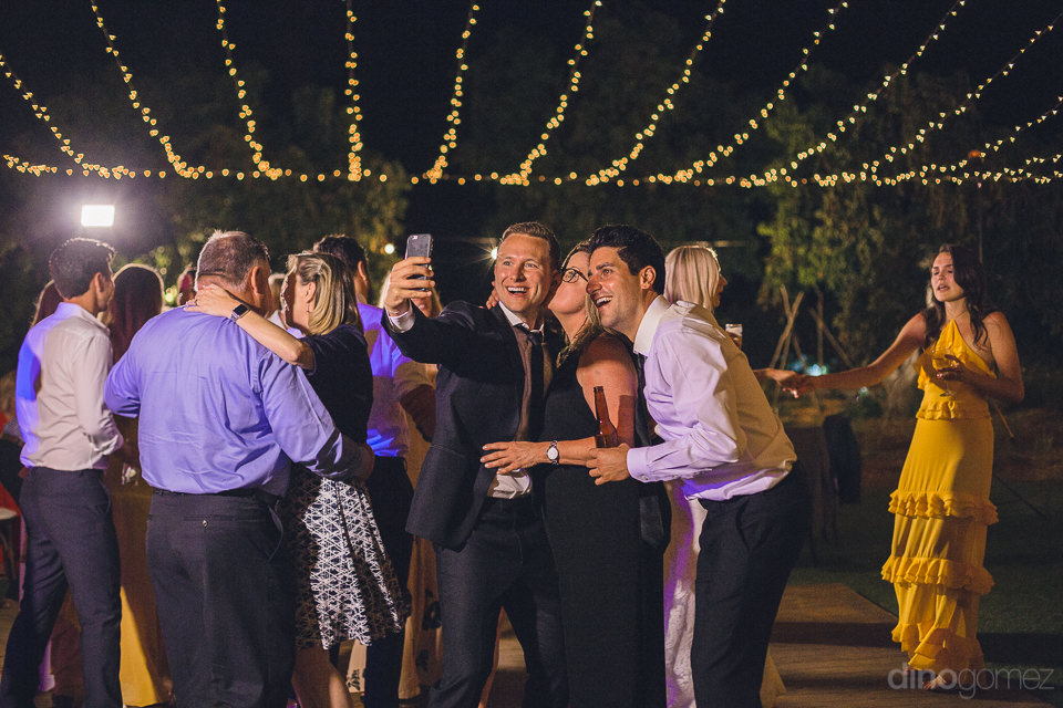 groom takes selfie with guests at wedding reception on dance flo