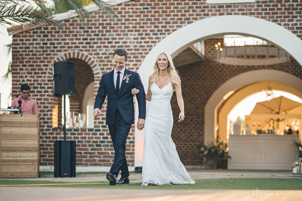 newlyweds smile as they walk to their dinner table at flora farm