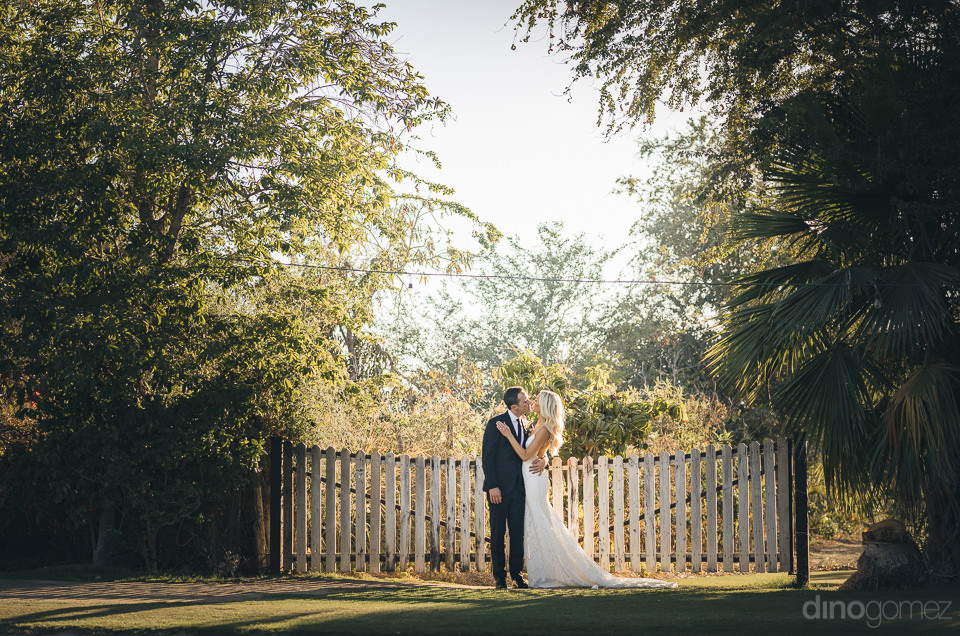 newlyweds kiss in front of quaint white picket fence at farm wed