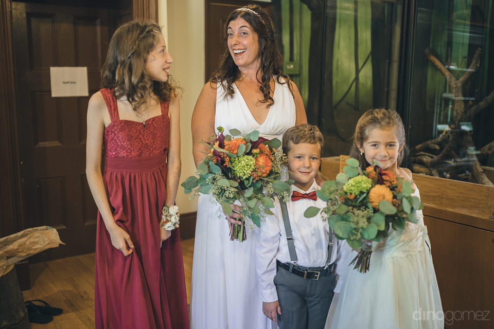 bride in white dress with flower girl and ring boy arriving to w