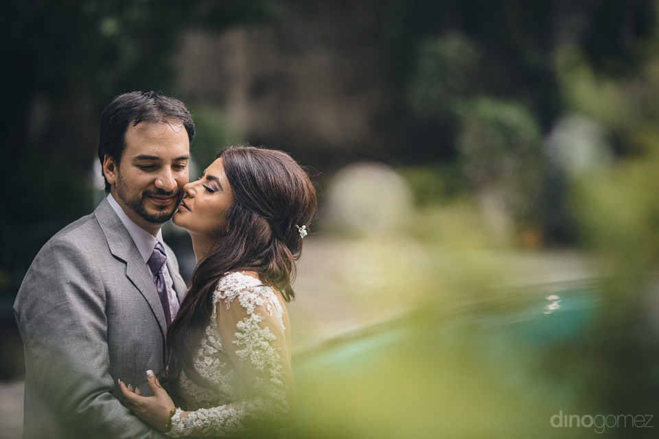 bride kisses groom by the pool at historic mexican hacienda in w