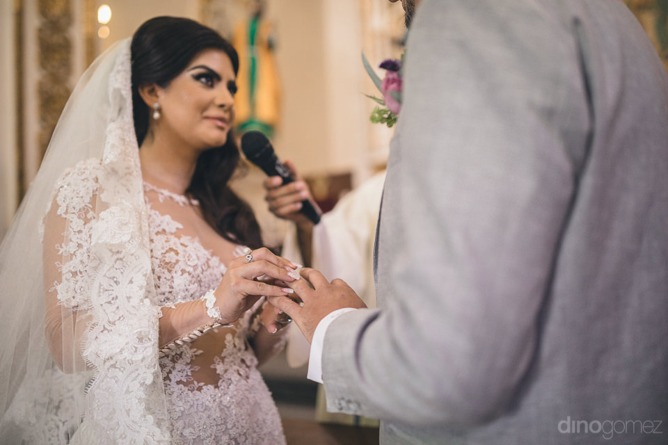 bride puts ring onto grooms finger speaks marriage vows