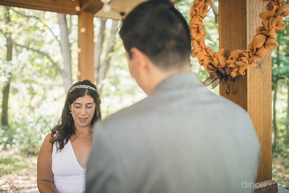 bride reading her marriage vows while groom listens intently at
