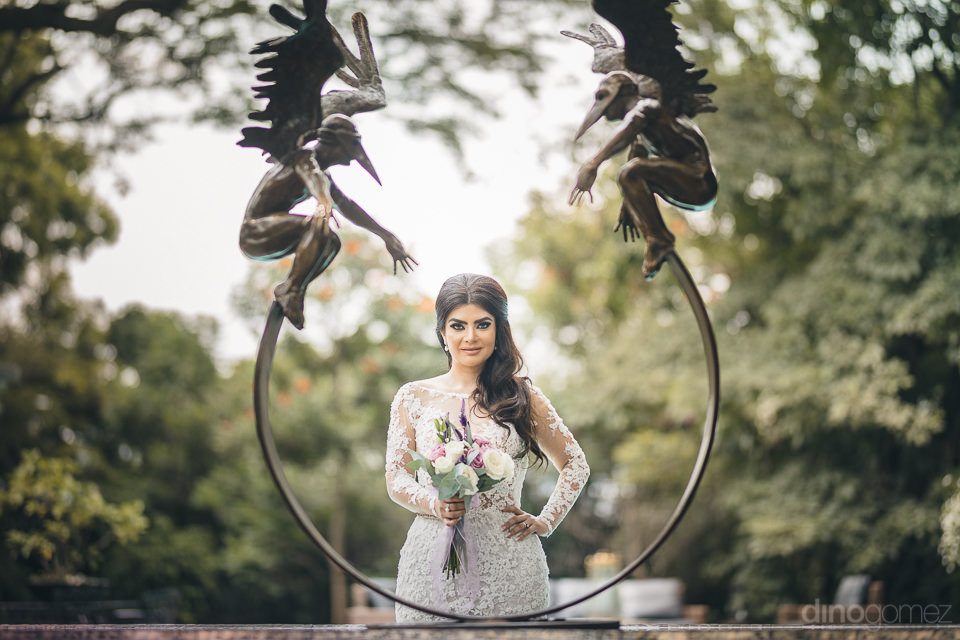 beautiful bride poses behind metal sculpture in artistic wedding