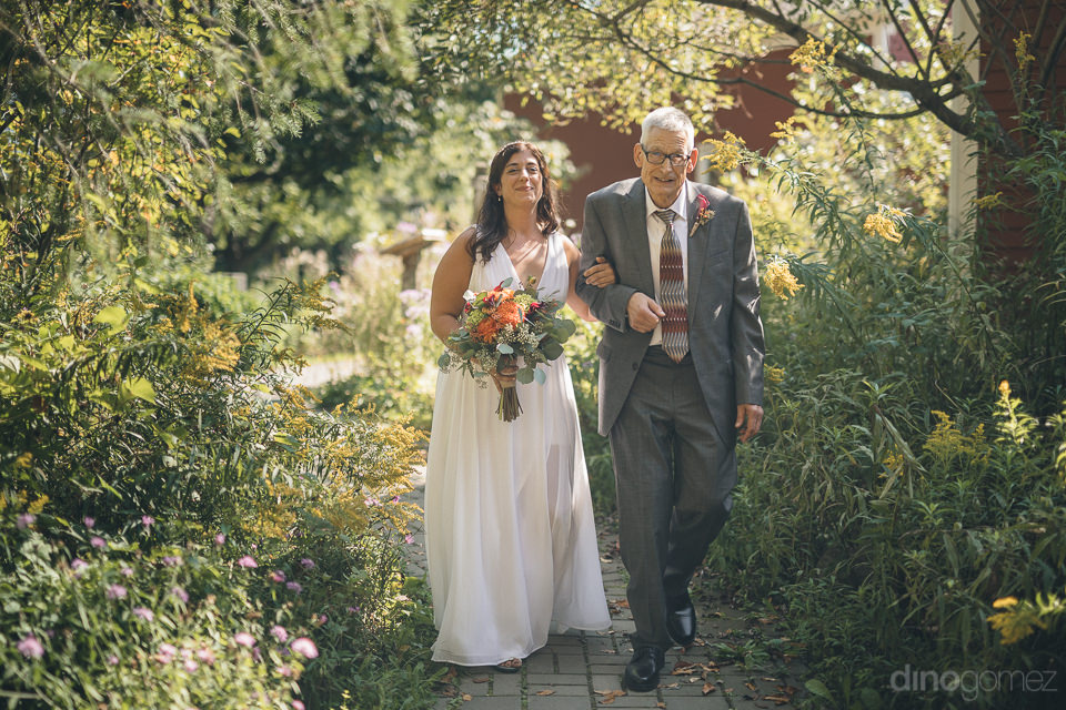 bride walks down aisle with father in forest wedding photographe