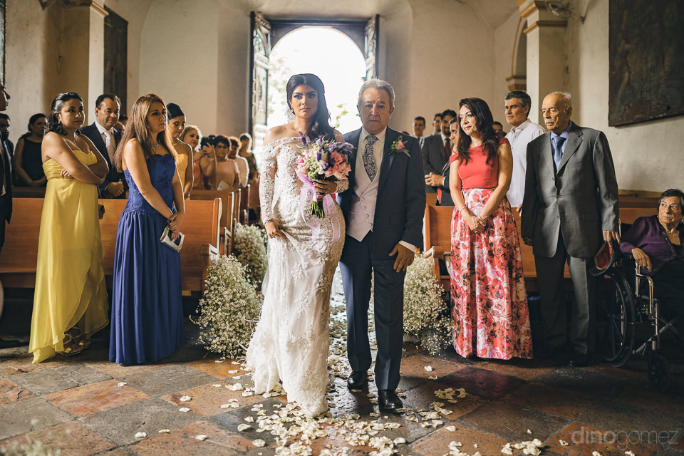 mexican bride walks down aisle accompanied by her father at chur