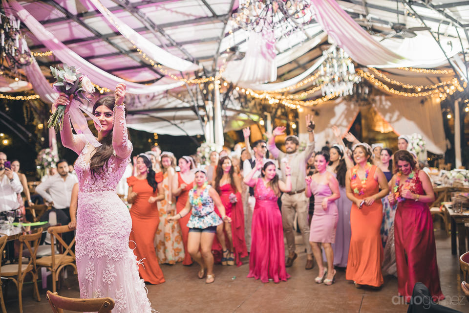 wedding guests line up behind the bride to catch her bouquet at