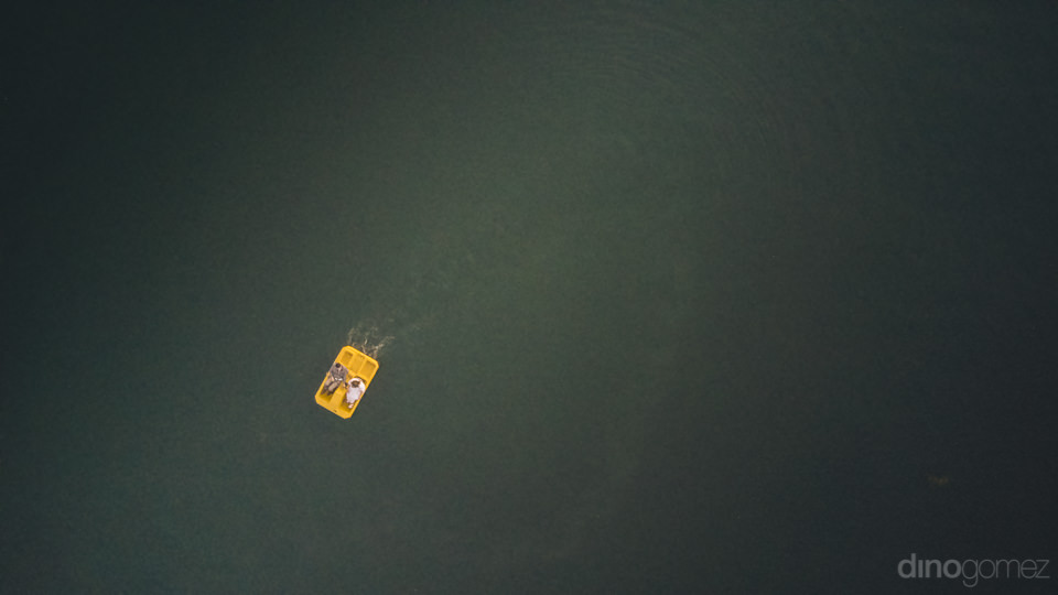 newlyweds in yellow paddle boat photo from above calm blue lake