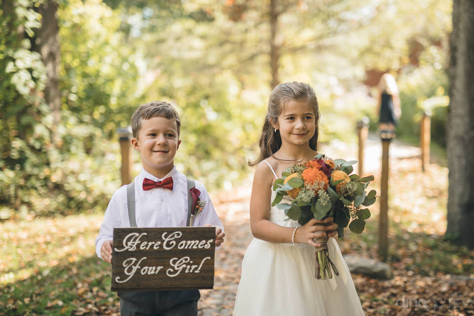 outdoor wedding by a lake in new york state ring boy and flower