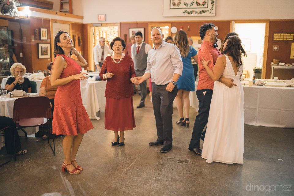 newlyweds with wedding guests dancing on dance floor at nature c