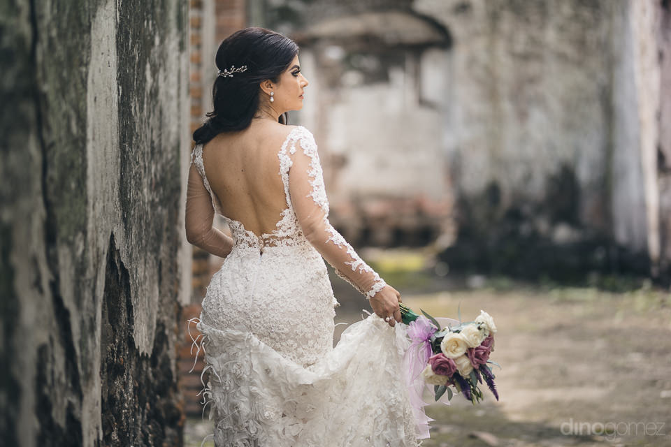 bride holds her bouquet in one hand with her back to the camera