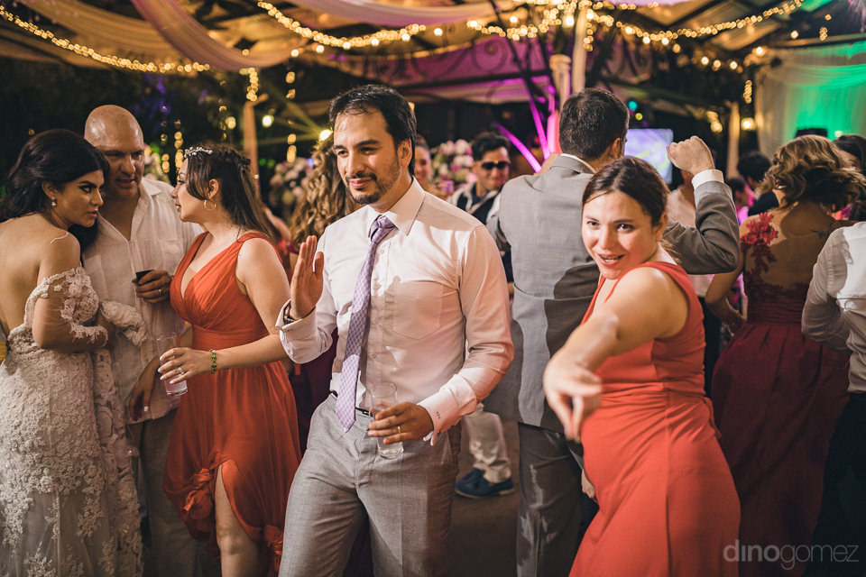 groom and guests dance while bride chats with friends