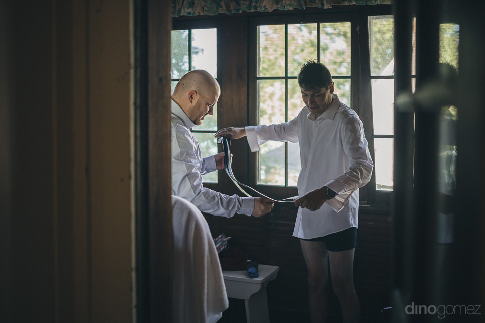 groom getting ready for his wedding in the woods in new york pho