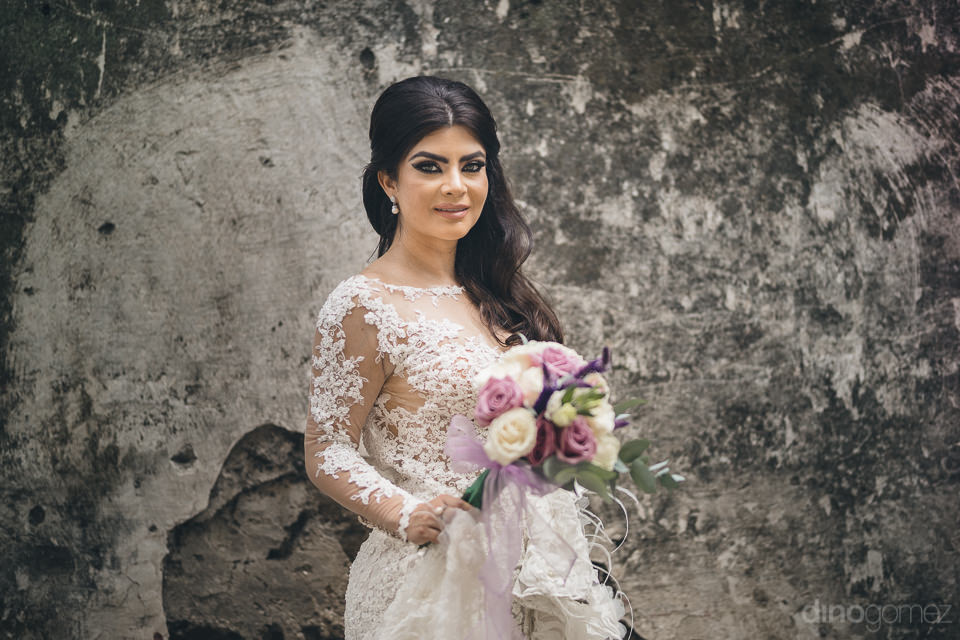 bride stands against old gray wall of historic mexican hacienda