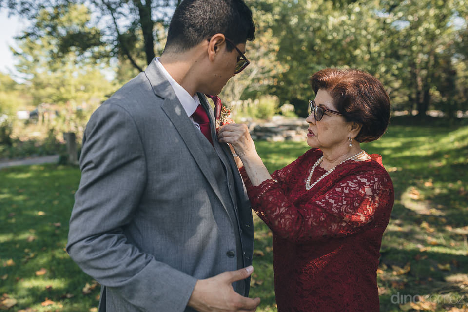 groom gets help with his boutonniere in serene new york forest w