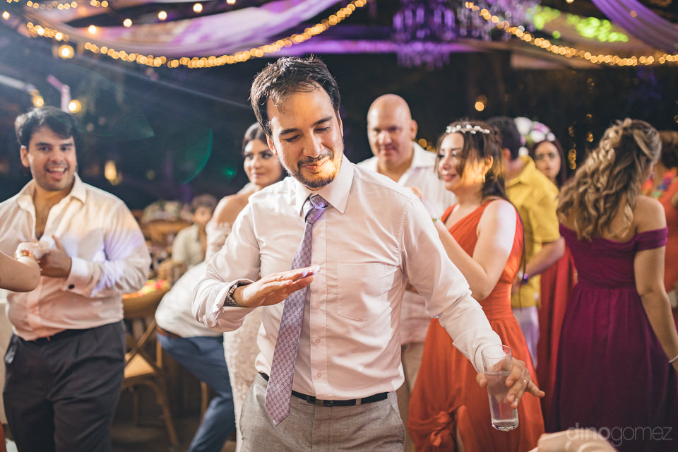 groom dances and parties with his friends at his wedding recepti