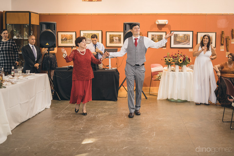 groom dancing with mother at wedding reception in nature center