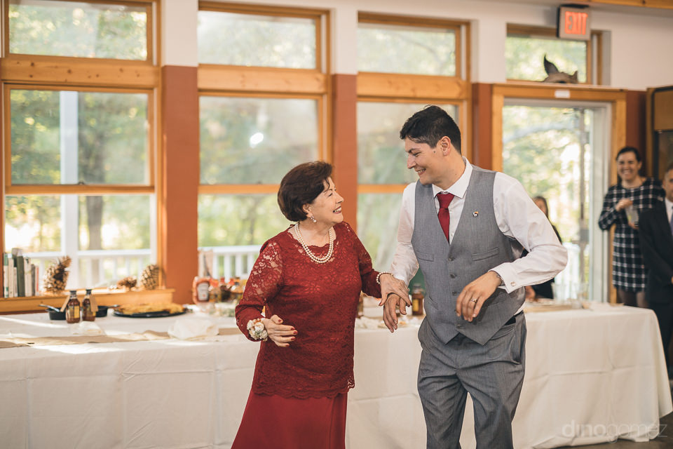 groom and mother laugh and smile at happy wedding reception in n