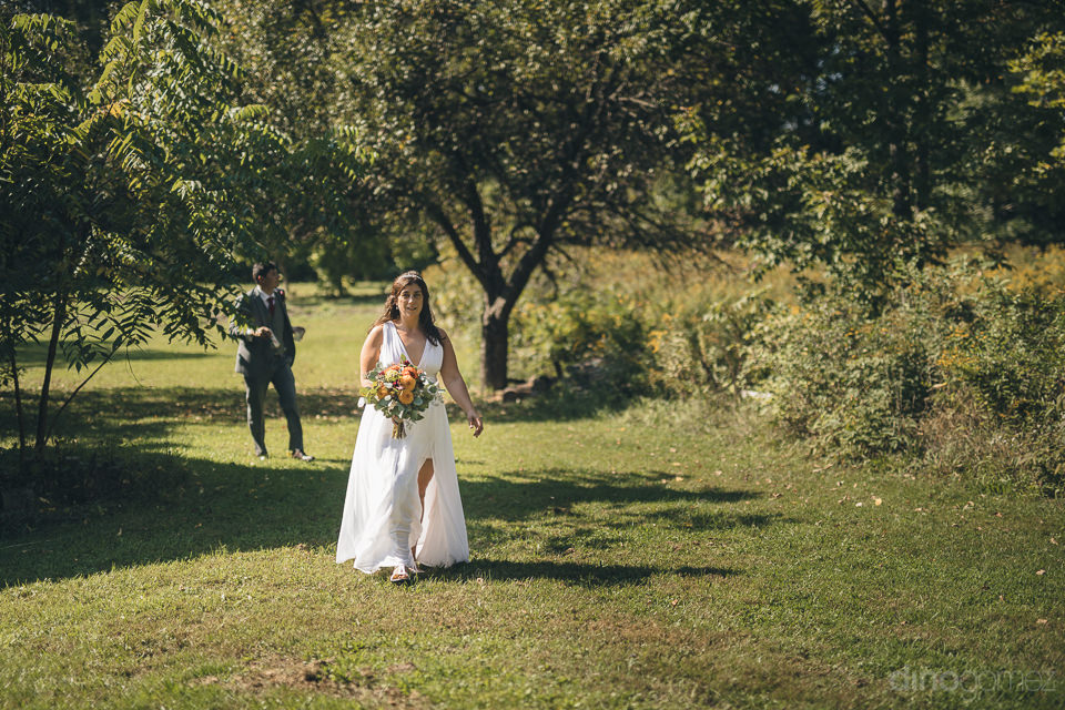 groom walks after bride through beautiful sunny field in summer