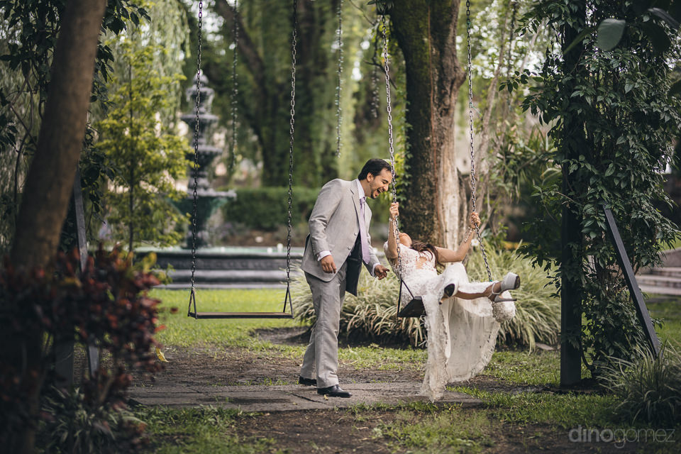 groom pushes bride on swing in green lush garden of mexican haci