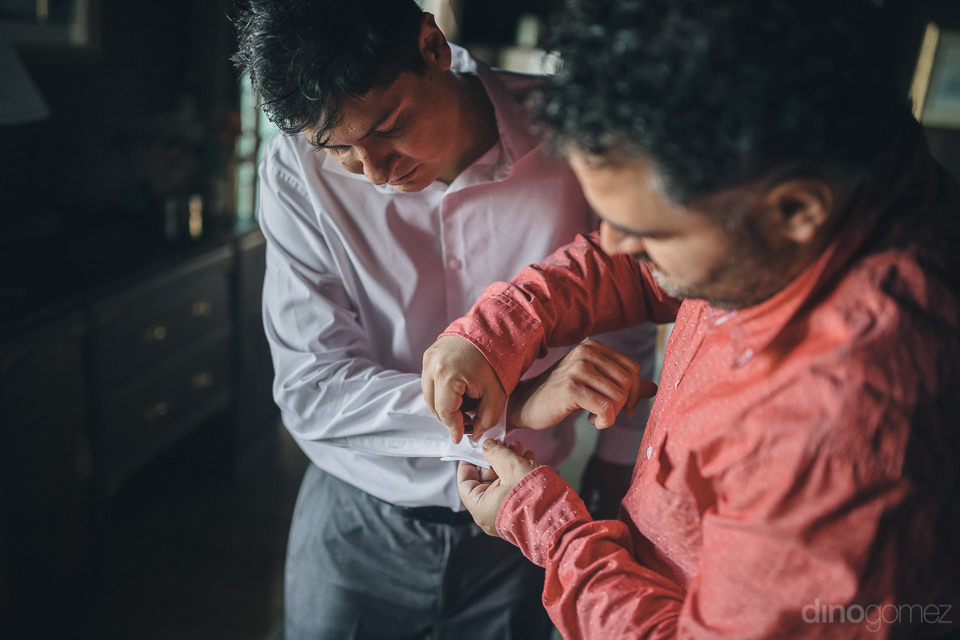 groom getting help putting the cufflinks on his shirt before his