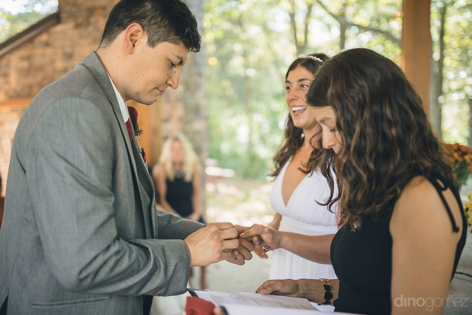 groom puts ring on brides finger at nature reserve wedding photo
