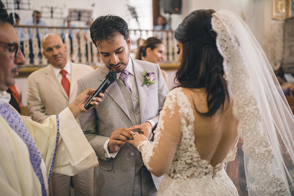 wedding ceremony in mexico church groom puts ring on brides fing
