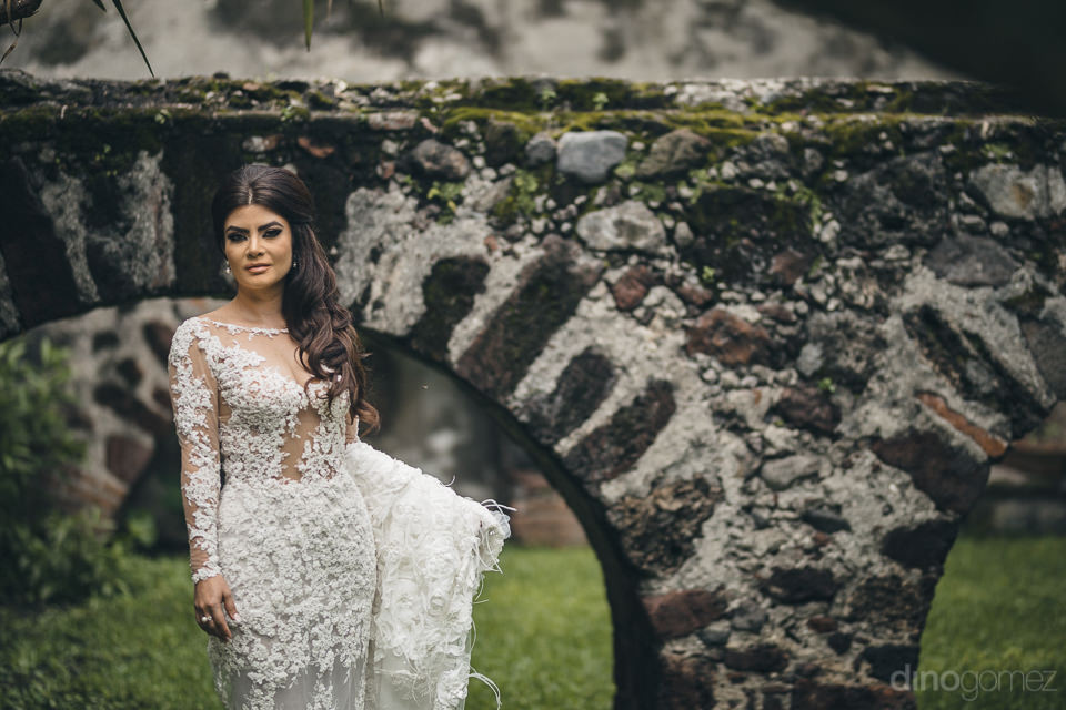 bride in white wedding dress in courtyard of rustic mexican haci
