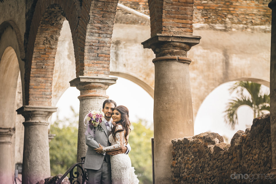 newlyweds standing in courtyard of historic mexican hacienda cas