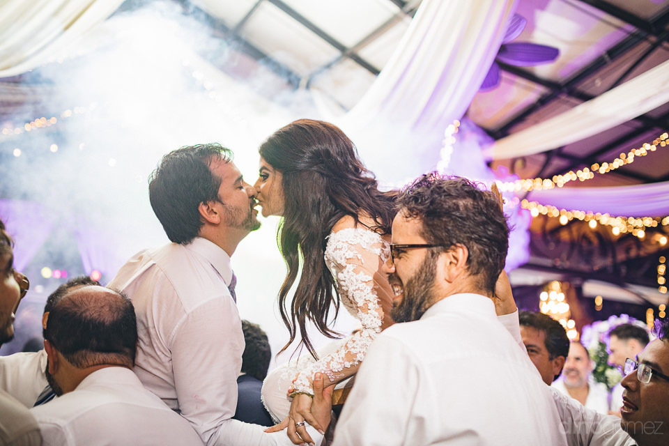 newlyweds lifted up and kiss in fun wedding photo by dino gomez