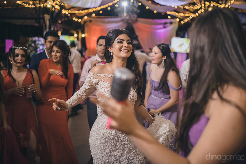 mexican bride on dance floor with guests during her wedding rece