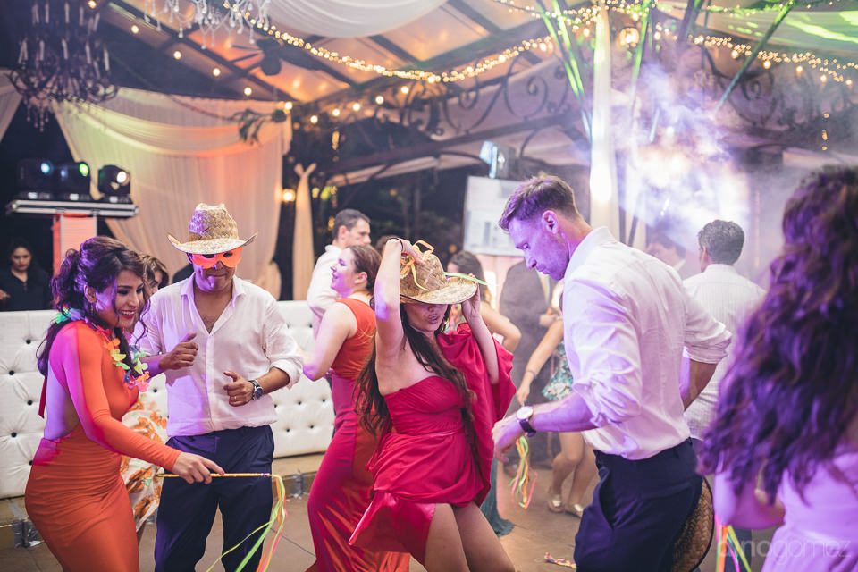 guests in hats and masks dance and party at mexican wedding phot