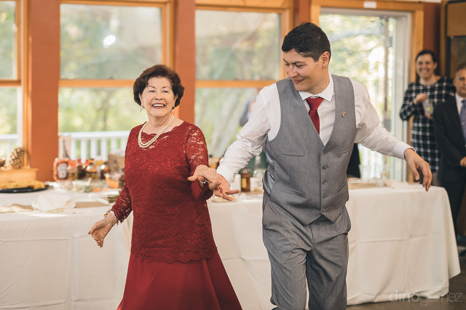 mother of groom dances with son at wedding reception photographe