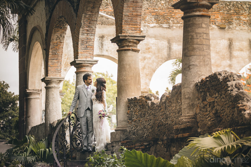 newlyweds stand alongside stone pillars in courtyard of rustic m