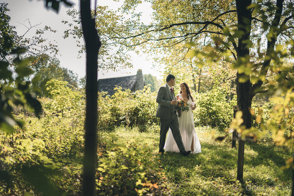 newlyweds standing in lush green forest on wedding day in new yo