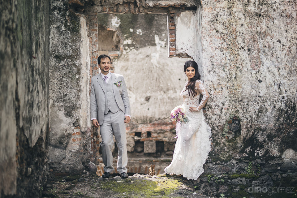 bride and groom lean on opposite sides of a rustic doorway in a