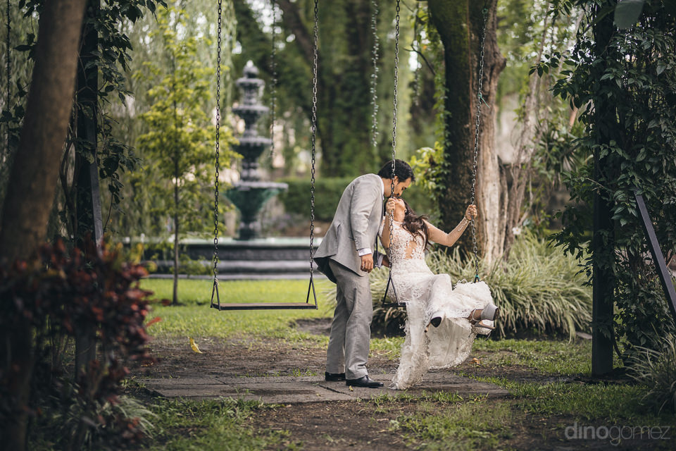 newlyweds kiss on swing set in garden with fountain in the backg
