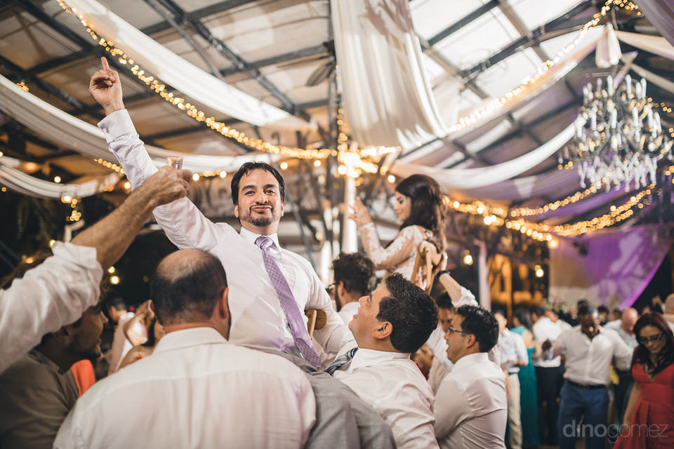 newlyweds lifted up in the air on the shoulders of wedding guest